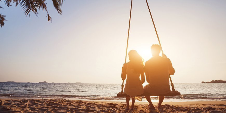 Honeymoon travel, silhouete of couple in love on the beach.